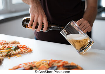 Close-up photo of a man pours beer into a glass. Next to the table is a pizza.