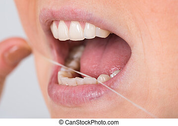 Woman Flossing Teeth - Close-up Photo Of A Woman Flossing...