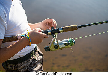 Close-up photo of a young boy fishing outdoors on a summer day.