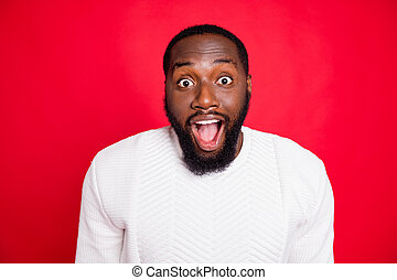 Close up photo of amazed surprised dark skin man hear wonderful incredible news about xmas discounts scream wow omg wear white pullover isolated over red color background