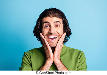 Close up photo of astonished person arms on chin open mouth green pullover isolated on blue color background