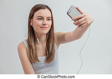 close up photo of beautiful hipster girl looking at herself from the smartphone