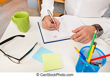 Close up photo of businessman making notes in his notepad