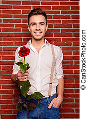 Close up photo of cheerful young man with rose