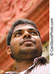 Close-up photo of confident, thinking business man of asian/indian origin. The person is wearing a formal shirt & the picture is shot with a building in the background