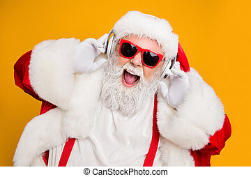 Close up photo of crazy funny santa claus listen music on modern headset celebrate christmas time noel party wear red trendy hat headwear isolated over shine color background