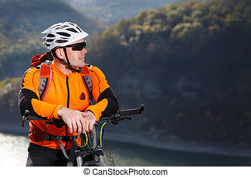 Close-up photo of cyclist in orange jacketr stands with his bike under river against beautiful landscape with mountain.
