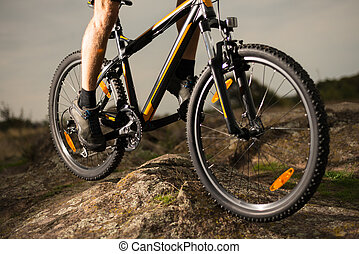 Close up Photo of Cyclist Riding Bike Down the Rock. Extreme Sport and Enduro Biking Concept.