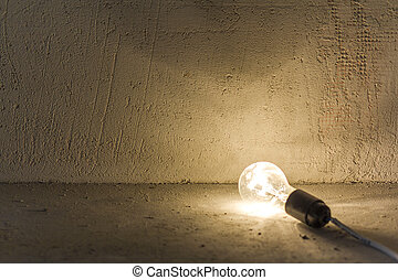Close up photo of electric bulb lying on the floor shining on fresh plastered gray rough wall showing defects. Electricity and repairing.