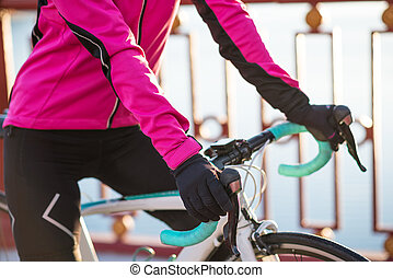 Close up Photo of Female Cyclist Hands in Gloves on Road Bicycle Handlebar in Cold Sunny Autumn Day. Healthy Lifestyle.