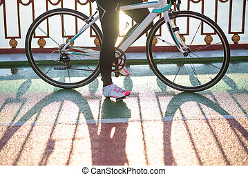 Close up Photo of Female Cyclist Legs and Road Bicycle Wheels in the Cold Sunny Autumn Day. Healthy Lifestyle Concept.