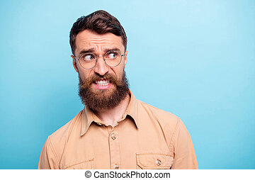 Close up photo of frustrated guy looking wearing brown shirt eyewear eyeglasses isolated over blue background