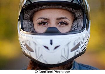 Close-up photo of girl in helmet with forest background