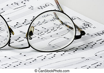 Close up photo of glasses on sheet music