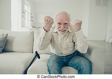 Close up photo of grey haired he his him grandpa with walking stick crazy fan of football soccer goal score glad fists raised wearing casual checkered shirt jeans denim outfit sitting on cozy divan
