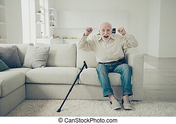 Close up photo of grey haired he his him grandparent with walking stick believe he can go without it wearing casual checkered shirt jeans denim outfit sitting on cozy divan