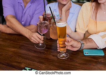 close-up photo of hands clinking glasses wit beer, alcoholic coctails