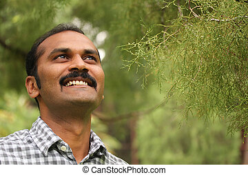 Close-up photo of hopeful, relaxed & happy asian/indian man...