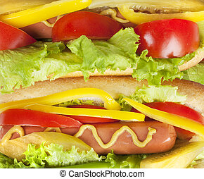 close up photo of hot dog with fresh tomato, salad, yellow peppers and pickled cucumber seasoned with mustard