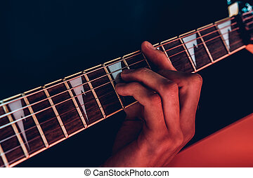 Close up photo of male hands playing guitar