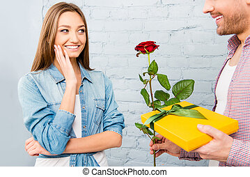 Close up photo of man giving gift and rose to his girl