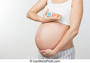 Close up photo of pregnant woman belly and wooden cubes