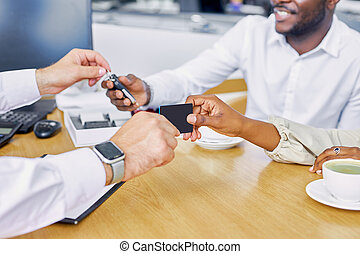 close-up photo of salesman's hand giving business card and keys to buyers