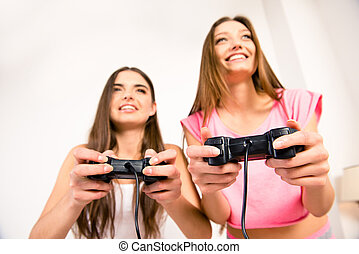 Close up photo of smiling cute friends playing video games