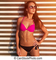 Close-up photo of tanned brunette model with sexy body standing in bikini and sunglasses against wall  wooden grating on hot summer day  sun shining brightly