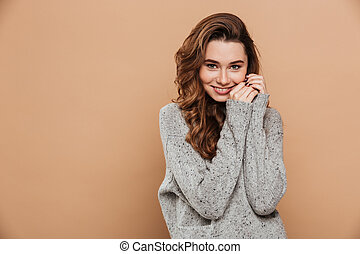 Close-up photo of tender smiling girl in soft knitted sweater looking at camera