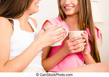 Close up photo of two young girls holding cups with coffee