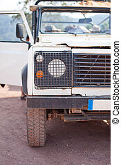 Close-up photo of white old suv at the off-road