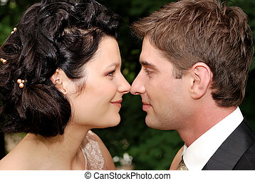 Close-up photo of young wedding couple. They are looking at...