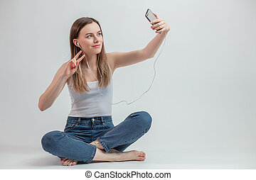 close-up photo og girl in earphones showing two fingers and taking a selfie