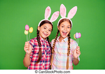 Close up photo portrait of cheerful amazed astonished pretty beautiful in checkered plaid bright shirts holding chocolate eggs in hands isolated bright vivid background