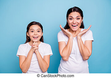 Close up photo pretty two people brown haired mum little daughter eyes mouth opened unbelievable yelling praying arms in air together wearing white t-shirts isolated bright blue background