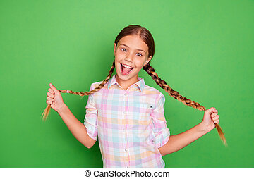 Close up photo small little age she her girl hold hand arm showing tails tongue out mouth positive optimistic pretty wear casual checkered plaid shirt isolated green bright vibrant vivid background