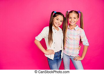 Close up photo two small little age girls best friends buddies hugging toothy smiling sweet wearing casual jeans denim checkered plaid shirts isolated rose vivid vibrant bright background