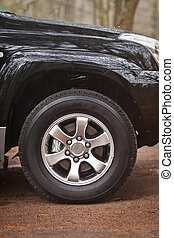Close-up photo wheel of an SUV that stands in the woods