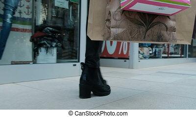 close-up photograph of woman legs walking along shopping center