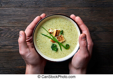 Close up pictire of man's hands holding bowl with home made vegetable soup on the dark wooden background.