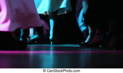 Close-up picture of adult people's feet moving it to music on the dancefloor at nightclub