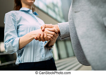 Close-up picture of businesswoman and businessman shaking hands