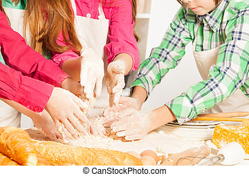 Close up picture of children's hands making dough