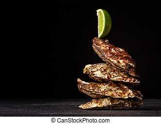 Close-up picture of four beautiful closed oysters on a black background. The greatest delicacy with lime. Copy space.