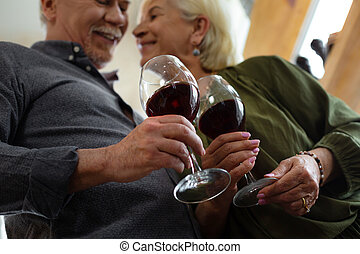 Close-up picture of married couple holding glasses of wine