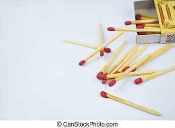 Close up picture of some flammable red fire matches scattered beside a small match box