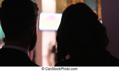 Close-up picture of young charming couple sweet talking at a night party in a club. Young man whispering something to his attractive woman and they have a talk at concert hall.