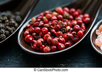 Close up pink peppercorn in spoon dark background