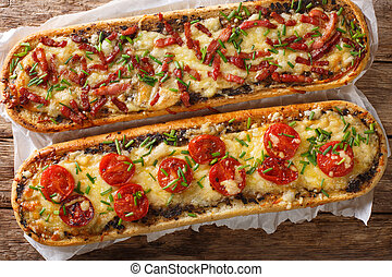 Close-up pizza sandwiches with bacon, mushrooms, tomatoes and cheese on a parchment. Horizontal view top